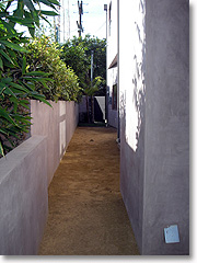 Decomposed granite path with concrete walls along side of house