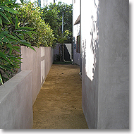 Concrete walls, stucco, and decomposed granite pathway